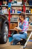 Μηχανική γυναίκα αυτοκινήτων στις μπλε φόρμες που μιλούν στο τηλέφωνο κοντά στο α Στοκ φωτογραφίες με δικαίωμα ελεύθερης χρήσης
