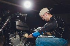 Μηχανική μηχανή επισκευής μοτοσικλετών κάτω από την καθοδήγηση εποπτ στοκ φωτογραφίες