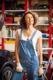 Μηχανική χαμογελώντας γυναίκα αυτοκινήτων με τα γαλλικά κλειδιά που στέκονται κοντά στο αυτοκίνητο Στοκ Φωτογραφία