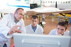 Μηχανικοί αεροσκαφών ομάδας που επισκευάζουν το αεριωθούμενο αεροπλάνο μερών στοκ εικόνα με δικαίωμα ελεύθερης χρήσης