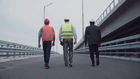 Μηχανικοί κατασκευής που περπατούν επάνω μια κεκλιμένη ράμπα εθνικών οδών φιλμ μικρού μήκους