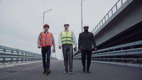 Μηχανικοί κατασκευής που περπατούν στην κεκλιμένη ράμπα εθνικών οδών απόθεμα βίντεο
