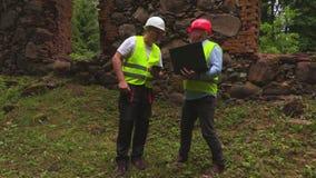 Μηχανικοί με το PC lap-top και ταμπλετών κοντά στις παλαιές καταστροφές τοίχων φιλμ μικρού μήκους