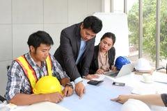 Μηχανικοί ομάδας που απασχολούνται στην αίθουσα συνεδριάσεων στο γραφείο Τρεις εργαζόμενοι μιλούν το σχέδιο κατασκευής Ξυλουργός  στοκ εικόνες