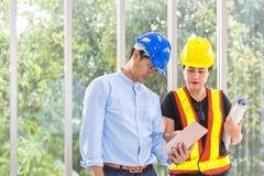 Μηχανικοί που απασχολούνται στην αίθουσα συνεδριάσεων με μια ταμπλέτα Δύο εργαζόμενοι προσέχουν το σχέδιο κατασκευής στο γραφείο  στοκ φωτογραφία