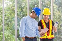 Μηχανικοί που απασχολούνται στην αίθουσα συνεδριάσεων με μια ταμπλέτα Δύο εργαζόμενοι προσέχουν το σχέδιο κατασκευής στο γραφείο  στοκ εικόνες