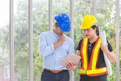 Μηχανικοί που απασχολούνται στην αίθουσα συνεδριάσεων με μια ταμπλέτα Δύο εργαζόμενοι προσέχουν το σχέδιο κατασκευής στο γραφείο  στοκ εικόνα