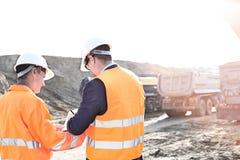 Μηχανικοί που γράφουν στην περιοχή αποκομμάτων στο εργοτάξιο οικοδομής ενάντια στο σαφή ουρανό Στοκ Φωτογραφία