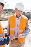Μηχανικοί που γράφουν στην περιοχή αποκομμάτων στο εργοτάξιο οικοδομής Στοκ φωτογραφία με δικαίωμα ελεύθερης χρήσης