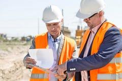Μηχανικοί που εξετάζουν τα έγγραφα σχετικά με την περιοχή αποκομμάτων στο εργοτάξιο οικοδομής ενάντια στο σαφή ουρανό Στοκ Εικόνες