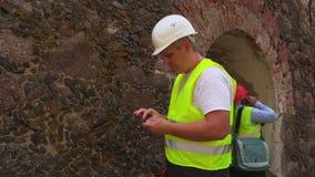 Μηχανικοί που επιθεωρούν τον παλαιό τοίχο απόθεμα βίντεο