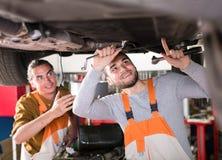 Μηχανικοί που επισκευάζουν το αυτοκίνητο με το γαλλικό κλειδί Στοκ Φωτογραφίες