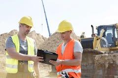 Μηχανικοί που διαβάζουν την περιοχή αποκομμάτων στο εργοτάξιο οικοδομής ενάντια στο σαφή ουρανό Στοκ εικόνες με δικαίωμα ελεύθερης χρήσης