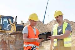 Μηχανικοί που διαβάζουν την περιοχή αποκομμάτων στο εργοτάξιο οικοδομής ενάντια στο σαφή ουρανό Στοκ Φωτογραφία