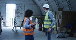 Μηχανικοί που μιλούν ενώ ρομπότ που λειτουργεί στο υπόβαθρο