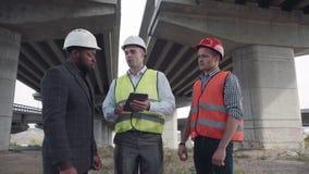 Μηχανικοί που στέκονται με το γενειοφόρο προϊστάμενο στο άσπρο σκληρό καπέλο απόθεμα βίντεο