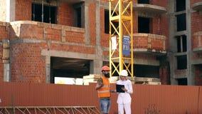 Μηχανικοί που συζητούν την οικοδόμηση του κτηρίου Νέος σύγχρονος γενειοφόρος μηχανικός ή αρχιτέκτονας με το θηλυκό οικοδόμο επάνω απόθεμα βίντεο