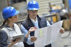 Μηχανικοί στις βιομηχανικές οδηγίες ανάγνωσης εργοστασίων στοκ φωτογραφίες