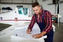 Μηχανικός αεροσκαφών που εργάζεται με τα σχέδια στοκ εικόνες