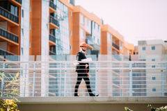 Μηχανικός αναδόχων περιοχών ατόμων Handome με το σκληρό καπέλο που κρατά το έγγραφο μπλε τυπωμένων υλών περπατώντας στο εργοτάξιο Στοκ Εικόνες