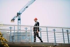 Μηχανικός αναδόχων περιοχών ατόμων Handome με το σκληρό καπέλο που κρατά το έγγραφο μπλε τυπωμένων υλών περπατώντας στο εργοτάξιο Στοκ Φωτογραφίες