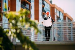 Μηχανικός αναδόχων περιοχών ατόμων Handome με το σκληρό καπέλο που κρατά το έγγραφο μπλε τυπωμένων υλών περπατώντας στο εργοτάξιο Στοκ Εικόνα