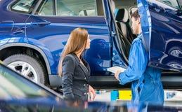 Μηχανικός αυτοκινήτων με να περάσει πελατών από τον πίνακα ελέγχου συντήρησης Στοκ εικόνα με δικαίωμα ελεύθερης χρήσης