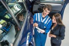 Μηχανικός αυτοκινήτων με να περάσει πελατών από τον πίνακα ελέγχου συντήρησης Στοκ φωτογραφία με δικαίωμα ελεύθερης χρήσης
