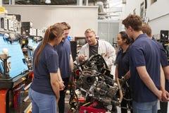 Μηχανικός αυτοκινήτων που παρουσιάζει μηχανές στους μαθητευόμενους στοκ εικόνα