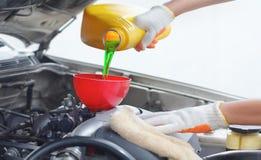 Μηχανικός αυτοκινήτων που χύνει το νέο πετρέλαιο στη μηχανή στοκ εικόνες
