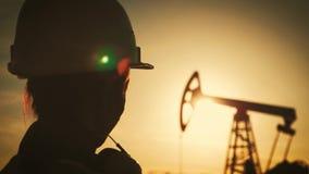 Μηχανικός γυναικών σκιαγραφιών που φορά τα άσπρα ενδύματα κρανών και εργασίας στο ηλιοβασίλεμα Βιομηχανικός, έννοια πετρελαίου κα απόθεμα βίντεο