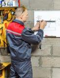 Μηχανικός εργαζόμενος που μελετά τις οδηγίες του Στοκ Φωτογραφία
