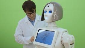 Μηχανικός ηλεκτρονικής που εργάζεται στην κατασκευή ρομπότ με την ταμπλέτα σε αργή κίνηση Φουτουριστική έννοια ρομπότ φιλμ μικρού μήκους