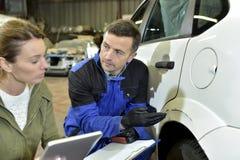 Μηχανικός και ασφαλιστής που συζητούν τις επιδιορθώσεις αυτοκινήτων στοκ φωτογραφία με δικαίωμα ελεύθερης χρήσης
