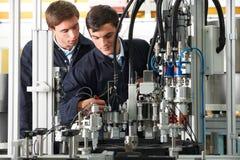 Μηχανικός και εκπαιδευόμενος που εργάζονται στον εξοπλισμό στο εργοστάσιο Στοκ Φωτογραφία