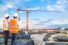 Μηχανικός και επιστάτης που εξετάζουν την κατασκευή γερανών με την ομιλία στοκ εικόνες