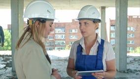 Μηχανικός και εργαζόμενος θηλυκών στο εργοτάξιο οικοδομής με το σχέδιο για την ψηφιακή ταμπλέτα απόθεμα βίντεο