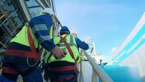 Μηχανικός και εργαζόμενος που αναρριχούνται στον πύργο ενός μεγάλου διυλιστηρίου πετρελαίου απόθεμα βίντεο
