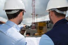 Μηχανικός και εργαζόμενος που ελέγχουν το σχέδιο στο εργοτάξιο οικοδομής Στοκ φωτογραφία με δικαίωμα ελεύθερης χρήσης