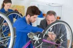 Μηχανικός και μαθητευόμενοι ποδηλάτων που επισκευάζουν το ποδήλατο στο εργαστήριο Στοκ εικόνες με δικαίωμα ελεύθερης χρήσης