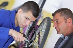 Μηχανικός και μαθητευόμενος ποδηλάτων που επισκευάζουν το ποδήλατο στο εργαστήριο Στοκ Εικόνες