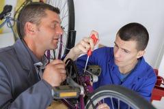 Μηχανικός και μαθητευόμενος ποδηλάτων που επισκευάζουν το ποδήλατο στο εργαστήριο Στοκ εικόνα με δικαίωμα ελεύθερης χρήσης