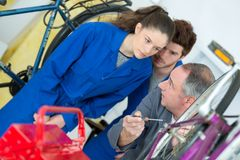 Μηχανικός και μαθητευόμενος ποδηλάτων που επισκευάζουν το ποδήλατο στο εργαστήριο Στοκ Φωτογραφία