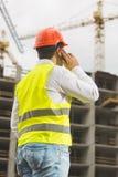 Μηχανικός κατασκευής που μιλά τηλεφωνικώς και που κοιτάζει στην οικοδόμηση του s Στοκ εικόνες με δικαίωμα ελεύθερης χρήσης