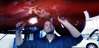 Μηχανικός λάμποντας φανός κάτω από το αυτοκίνητο στοκ εικόνες