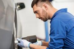 Μηχανικός με τη μεταβαλλόμενη ρόδα αυτοκινήτων κατσαβιδιών Στοκ εικόνες με δικαίωμα ελεύθερης χρήσης
