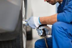 Μηχανικός με τη μεταβαλλόμενη ρόδα αυτοκινήτων κατσαβιδιών Στοκ Εικόνα