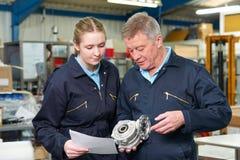Μηχανικός με το μαθητευόμενο που εξετάζει το συστατικό στο εργοστάσιο Στοκ φωτογραφία με δικαίωμα ελεύθερης χρήσης