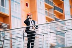 Μηχανικός με το σχέδιο στο χέρι του που μιλά στο τηλέφωνο κυττάρων από την πλευρά κατασκευής Στοκ εικόνες με δικαίωμα ελεύθερης χρήσης