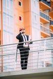 Μηχανικός με το σχέδιο στο χέρι του που μιλά στο τηλέφωνο κυττάρων από την πλευρά κατασκευής Στοκ φωτογραφία με δικαίωμα ελεύθερης χρήσης